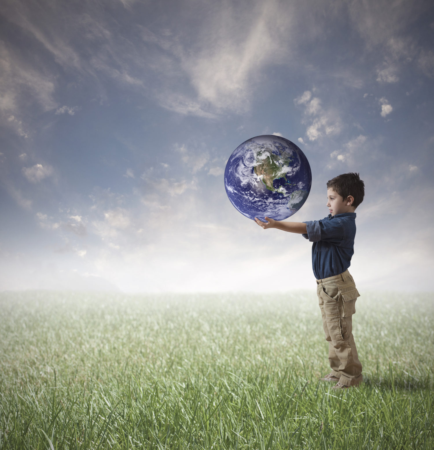 Standing boy holding earth imagining the world full of compassion and wisdom