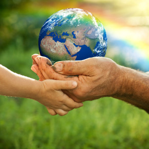 adult and child hands holding the earth