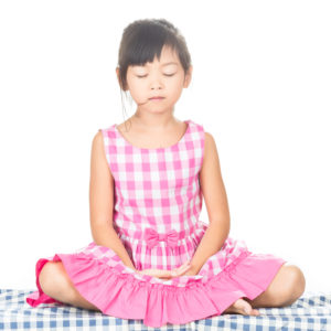 Young child in meditation with peaceful face