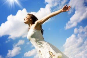 woman with arms open and smiling face. The sky is clear and blue like her mind.