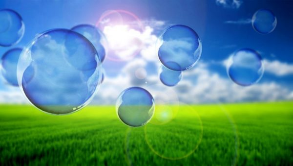 Bubbles floating above field with blue sky
