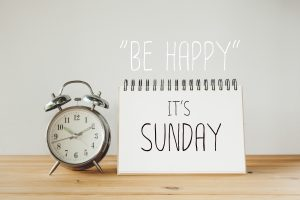 A clock and sign on a table. The sign reads 'be happy its Sunday'.