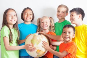 A group of children holding a model of the world